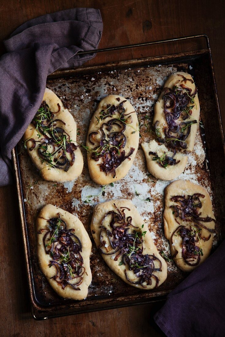 Yeast bread topped with red onions on a baking tray