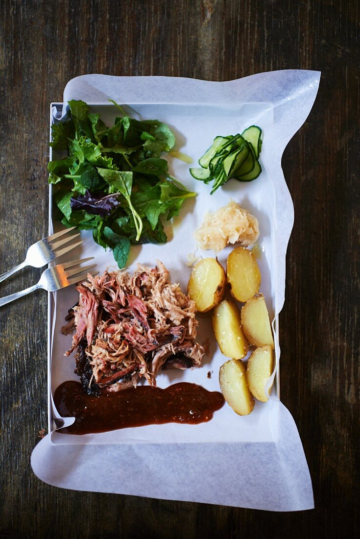 Barbecued pork with salad leaves and potatoes