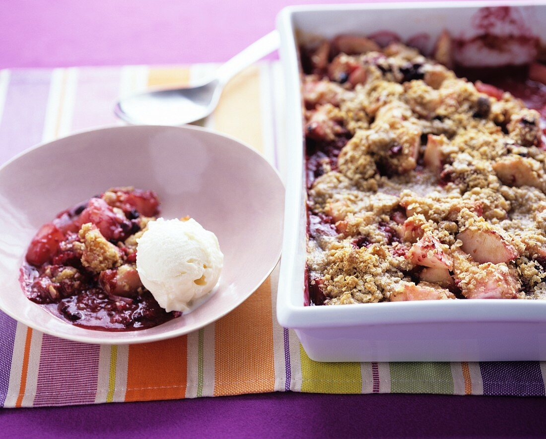 Rhubarb crumble in a baking tin and on a plate with vanilla ice cream