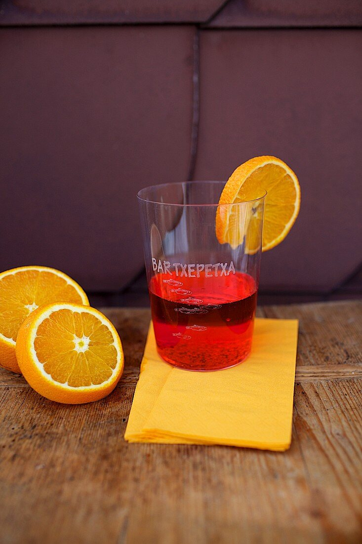 A plastic cup of Campari with a slice of orange