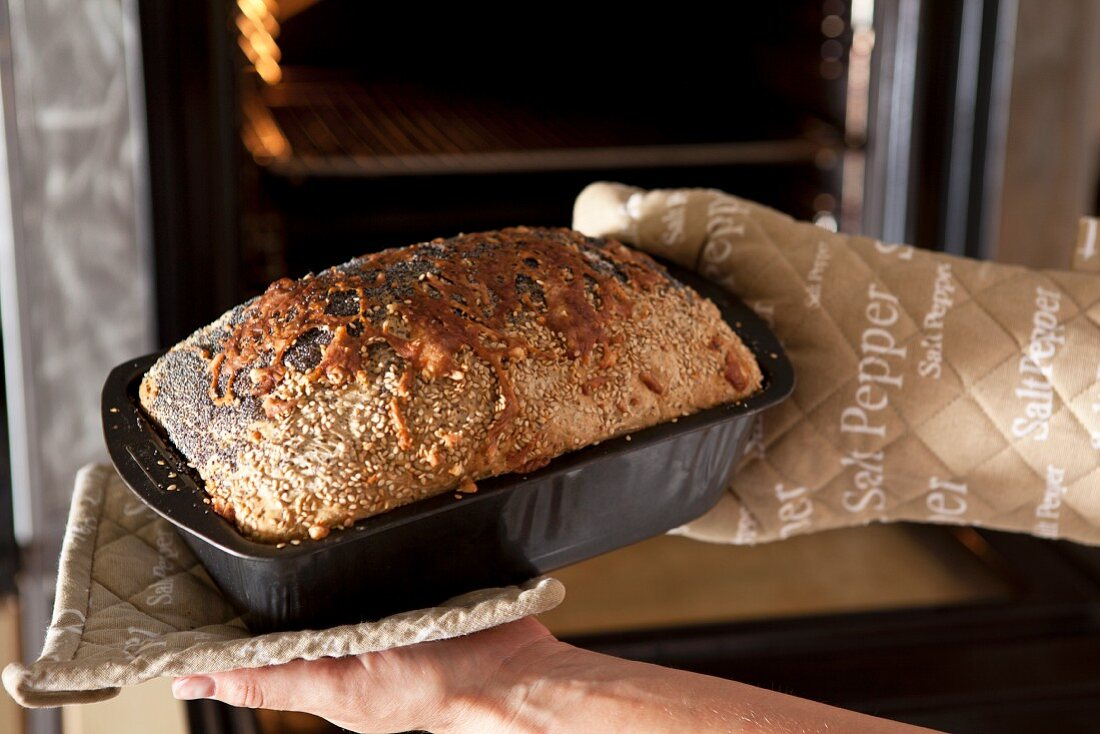 Hands holding a loaf tin with freshly baked wholemeal bread