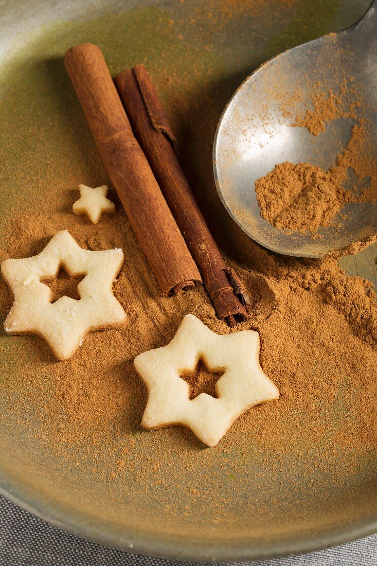 Star-shaped biscuits, ground cinnamon, cinnamon sticks and a spoon