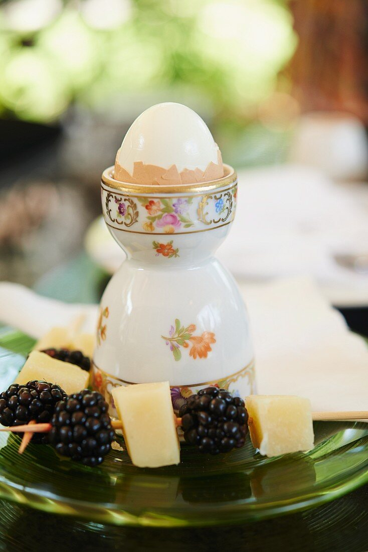 A Soft Boiled Egg with Skewers of Blackberries and Cheese