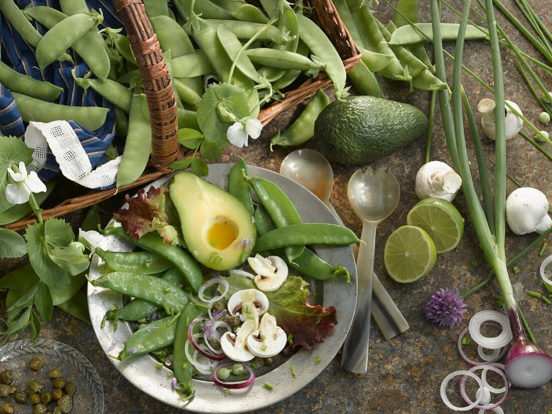 A still life featuring a plate of raw vegetables and sugar snap peas