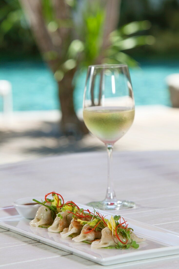 Dim Sum with prawn filling and a glass of wine on a table outdoors