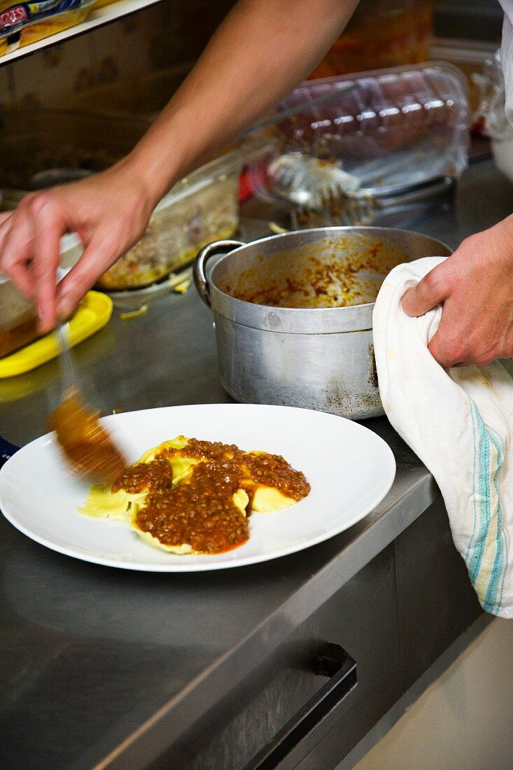 A chef dishing up ravioli and minced meat sauce in a commercial kitchen