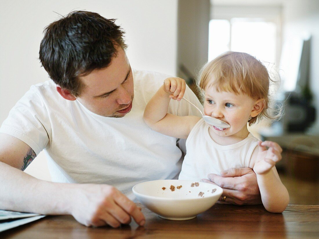 A girl sitting in her father''s lap, eating, Sweden.