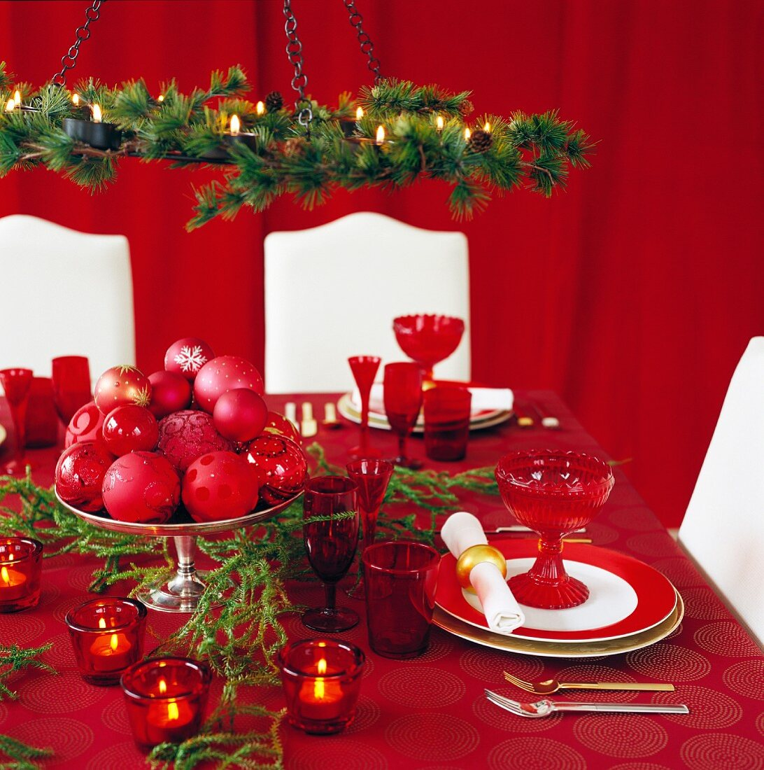 Festively set table and white upholstered dining chairs in front of red curtain