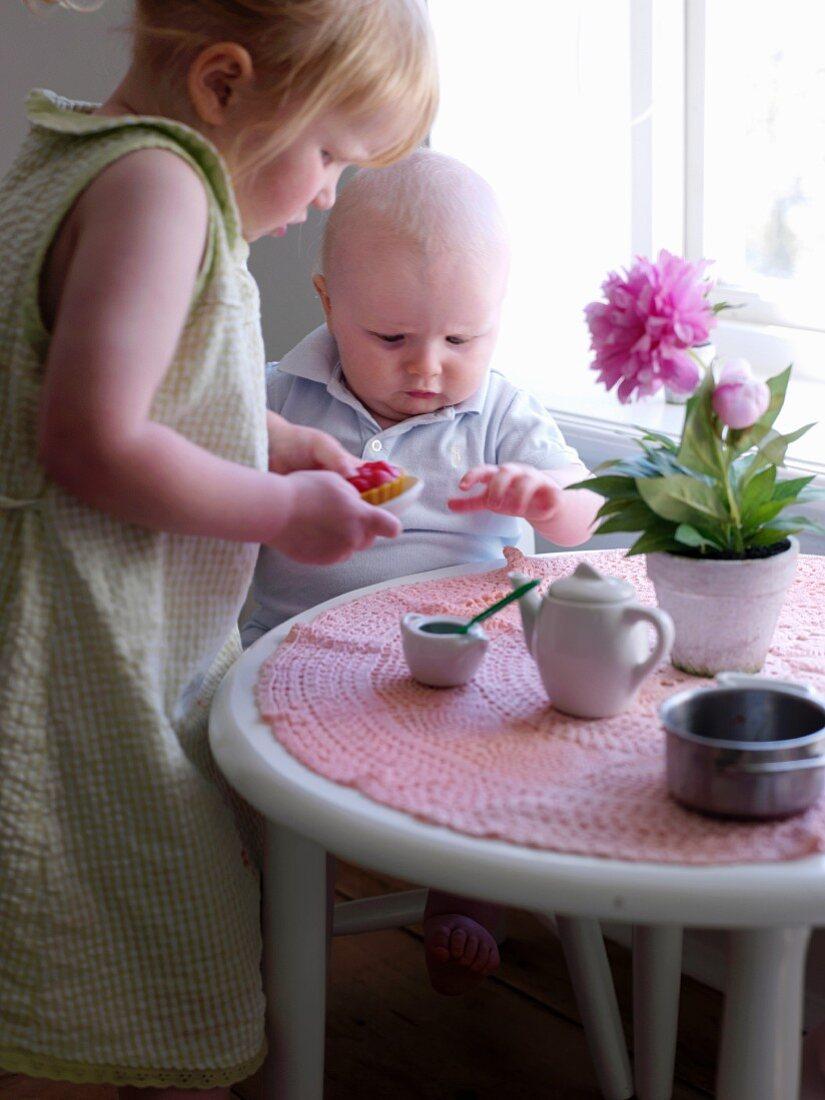 Little girl bringing baby a tart