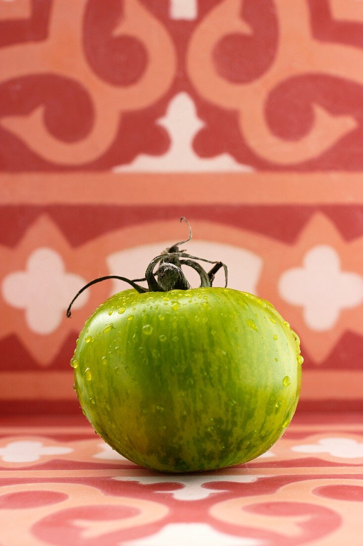 A green tomato with water droplets