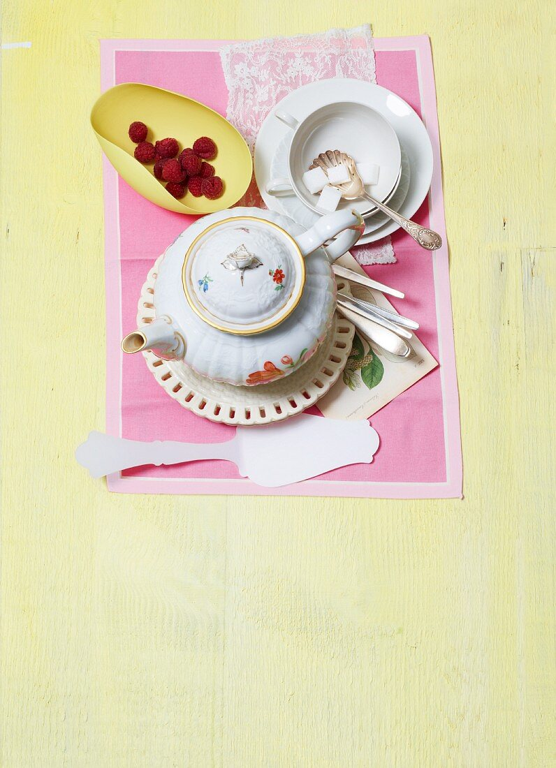 A coffee cup and pot, sugar cubes and raspberries