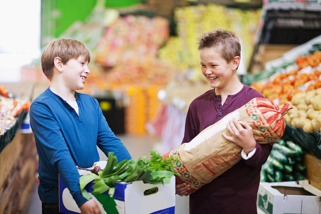 Young boys carrying vegetables in indoor market