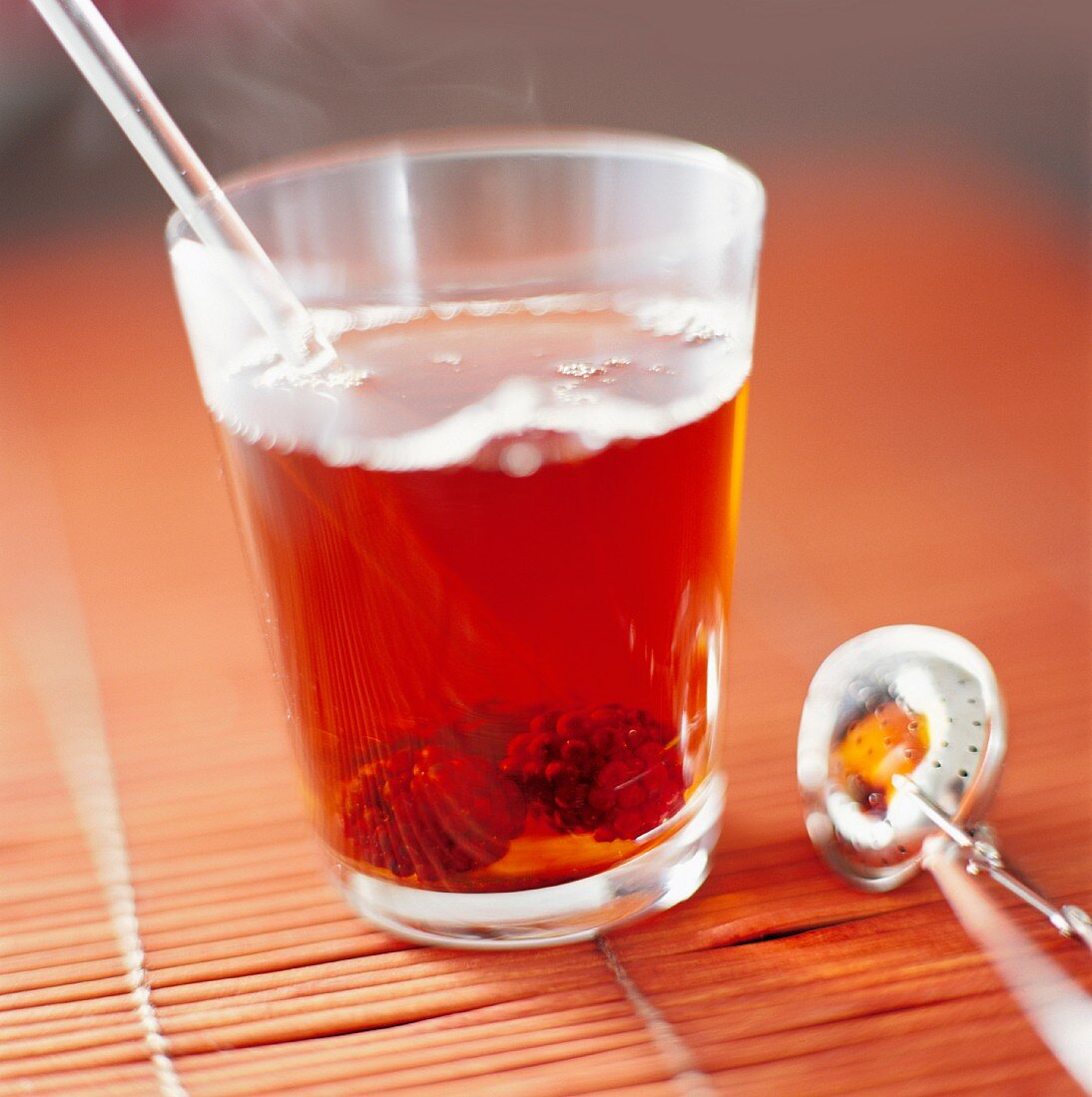 Fruit tea in a glass next to a tea ball