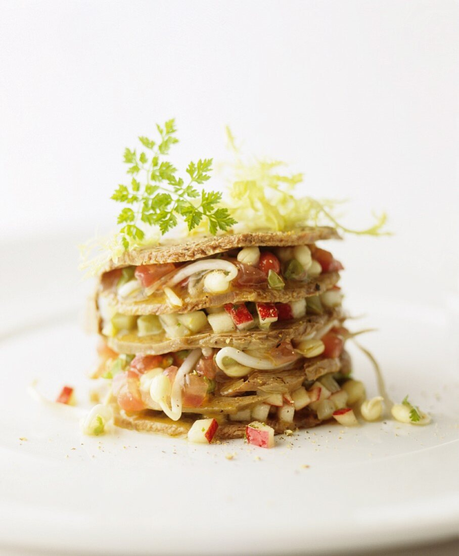 A tower of vegetable and apple tartare with edible shoots
