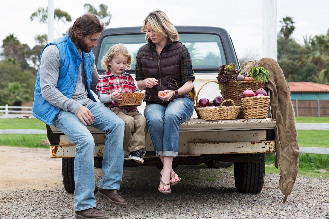 A family sitting with baskets of fruit and vegetables on the loading bed of a pick-up