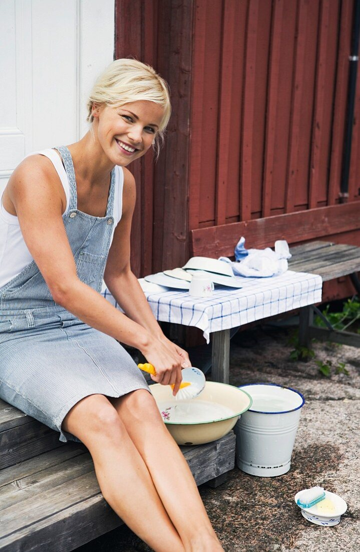 A woman washing the dishes outside a summer day, Sweden.