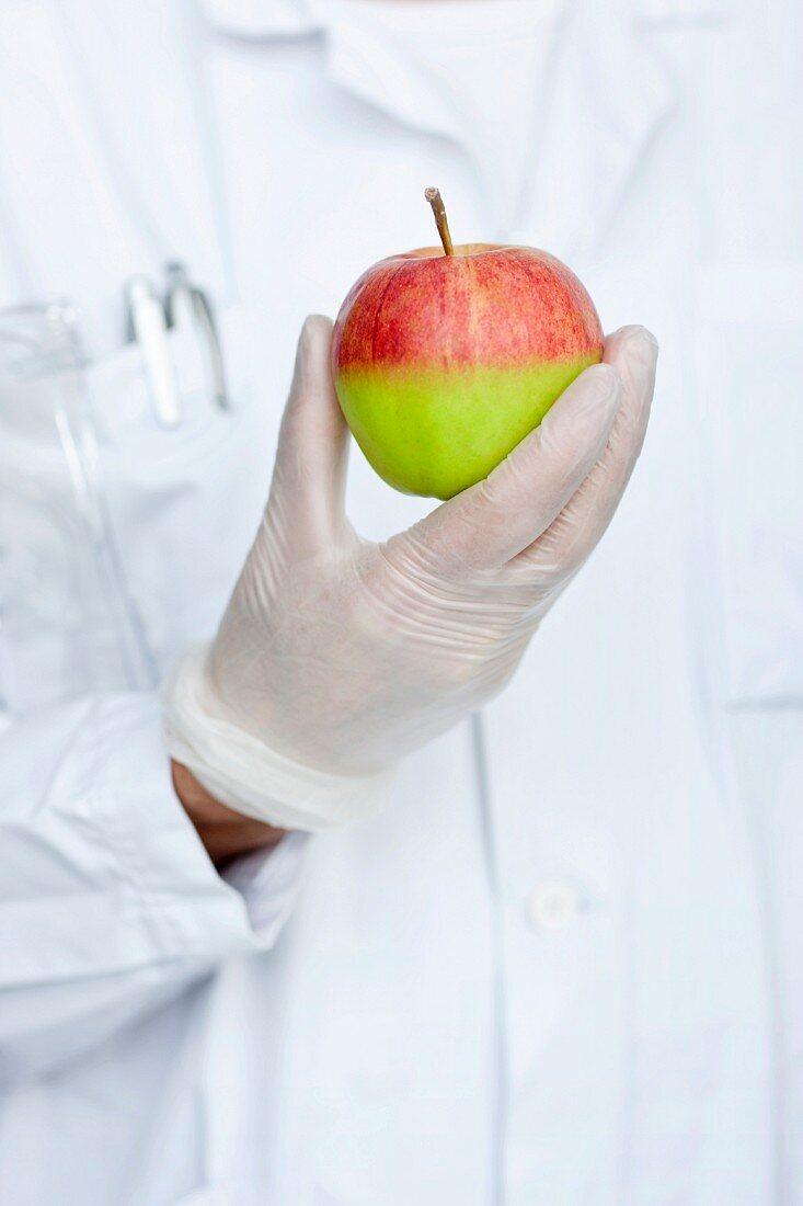 Laboratory technician holding apple