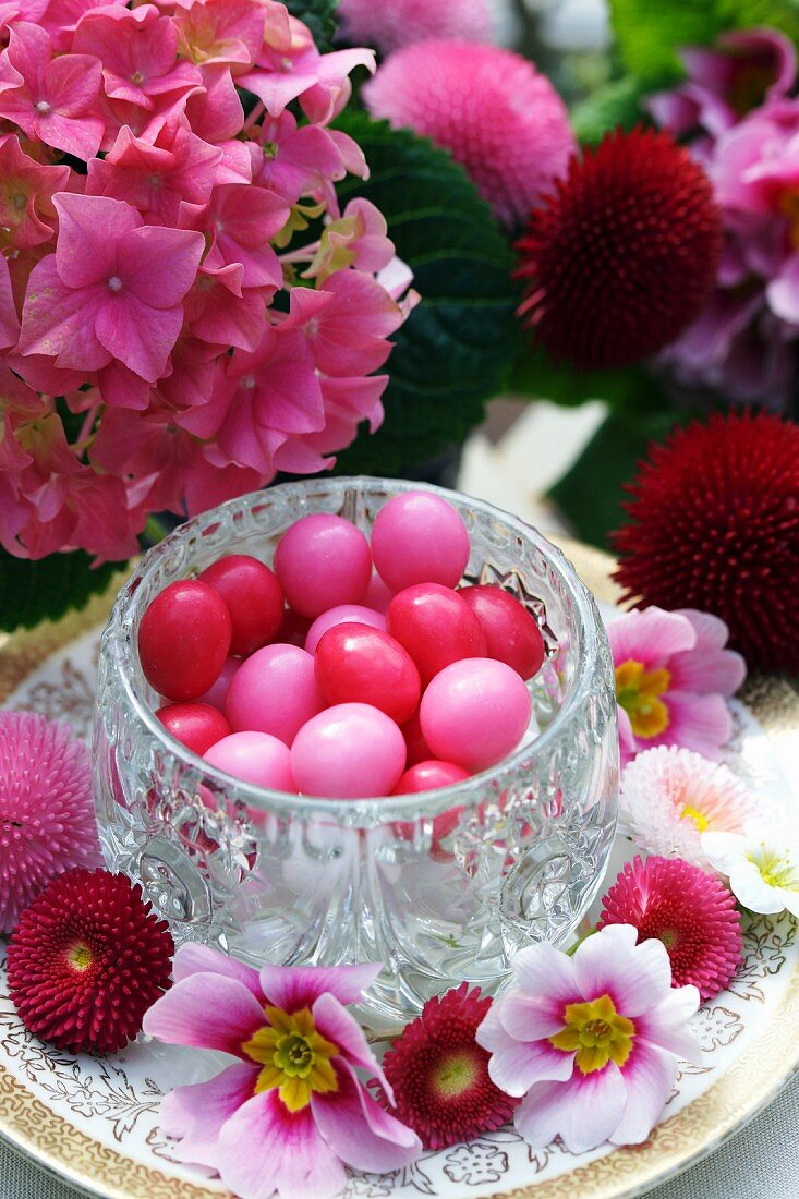 A crystal pot holding pale and bright pink sugar eggs, surrounded by spring flowers