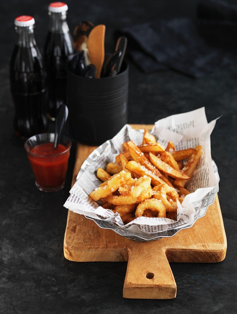Deep-fried squid rings and chips on newspaper