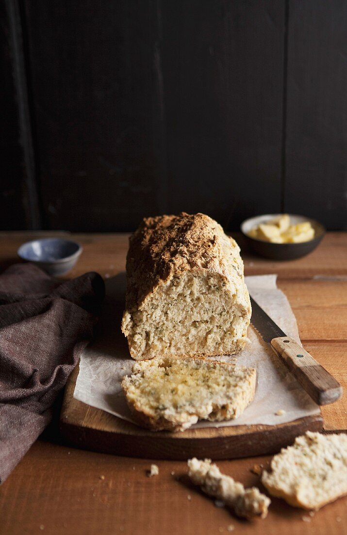 Beer bread, partly sliced on a woodenboard