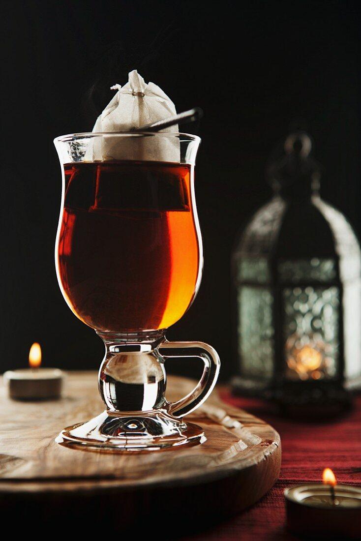 A glass of tea, a lantern and a tea light