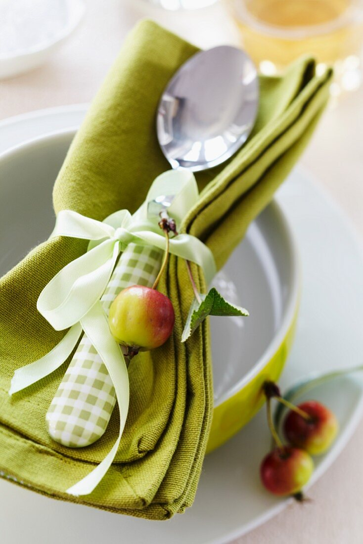A napkin and a spoon tied together with a ribbon and decorated with an ornamental apple