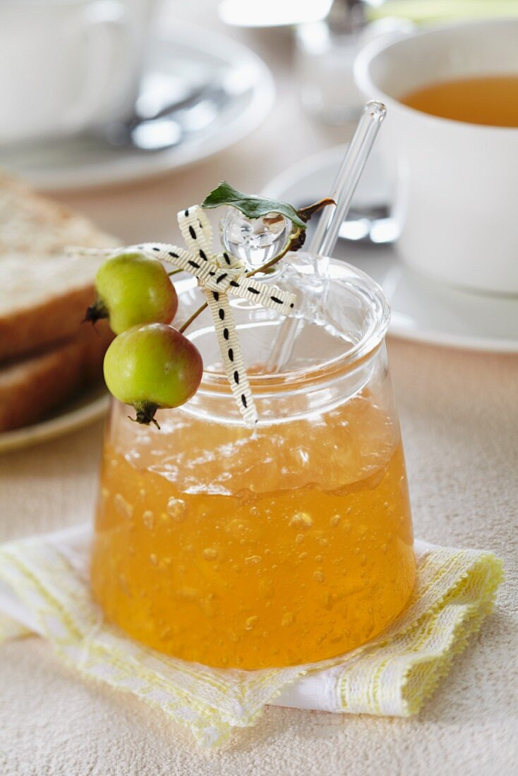 A jar of apple jelly on a breakfast table decorated with ornamental apples