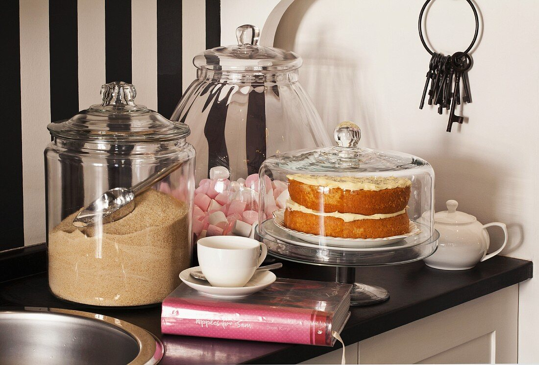 Brown sugar and marshmallows in glass jars and cake under glass cover on black kitchen worksurface