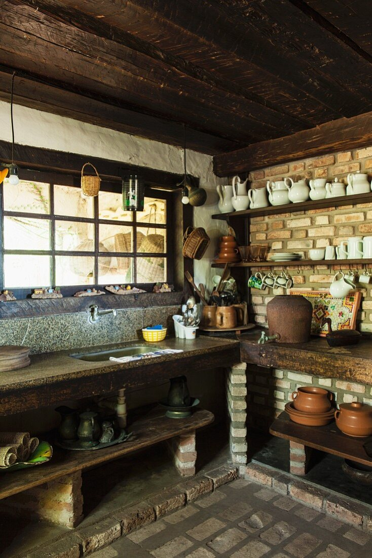 Ceramic pots and white crockery on shelves mounted on brick walls in rustic kitchen