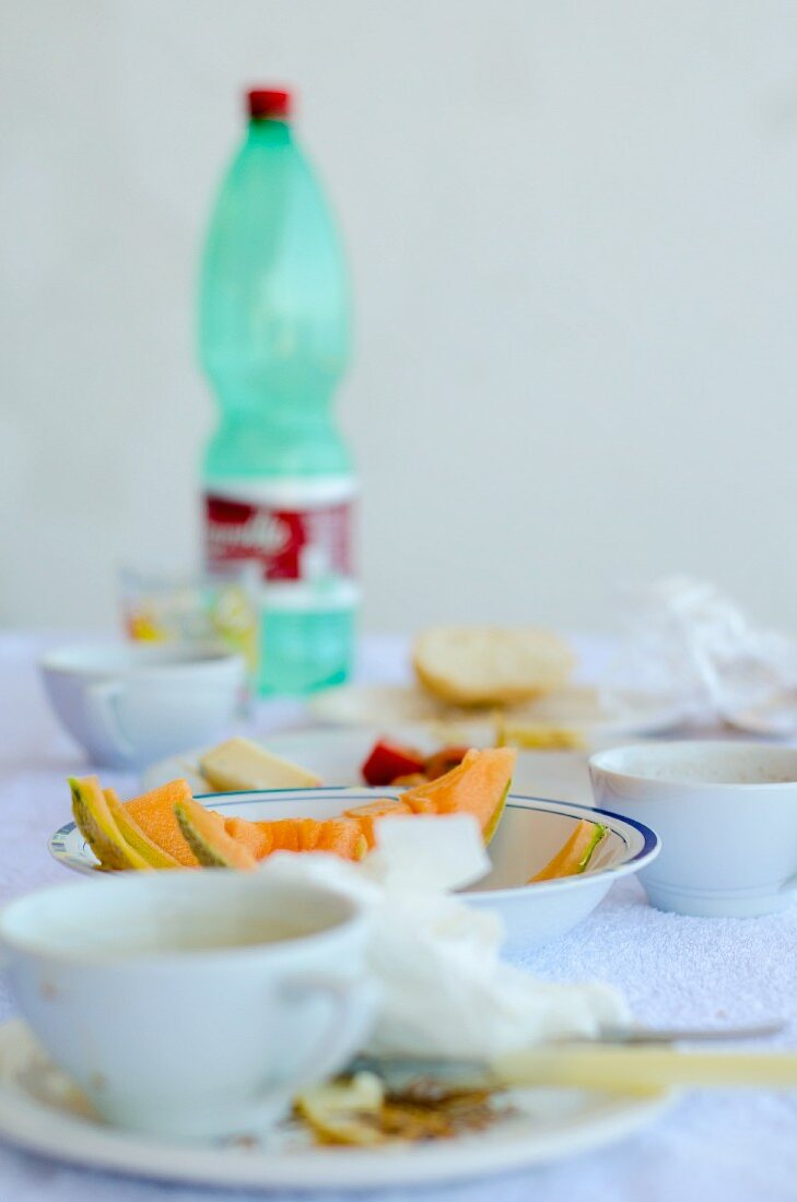 The remains of breakfast, with melon and a bottle of water