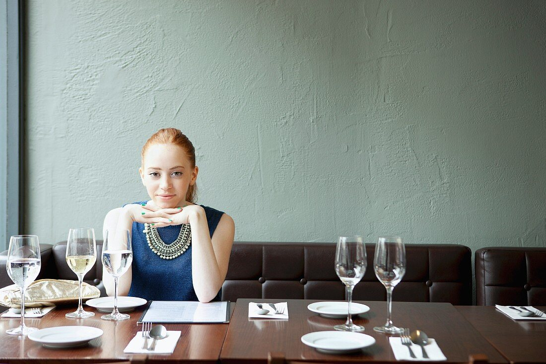 Young woman in restaurant, hands on chin