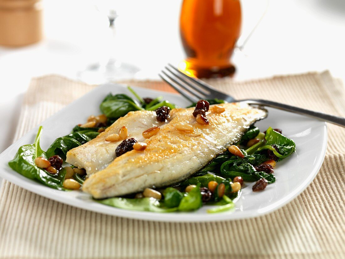 pan fried sea bass with wilted spinach, roasted pine nuts and sultanas