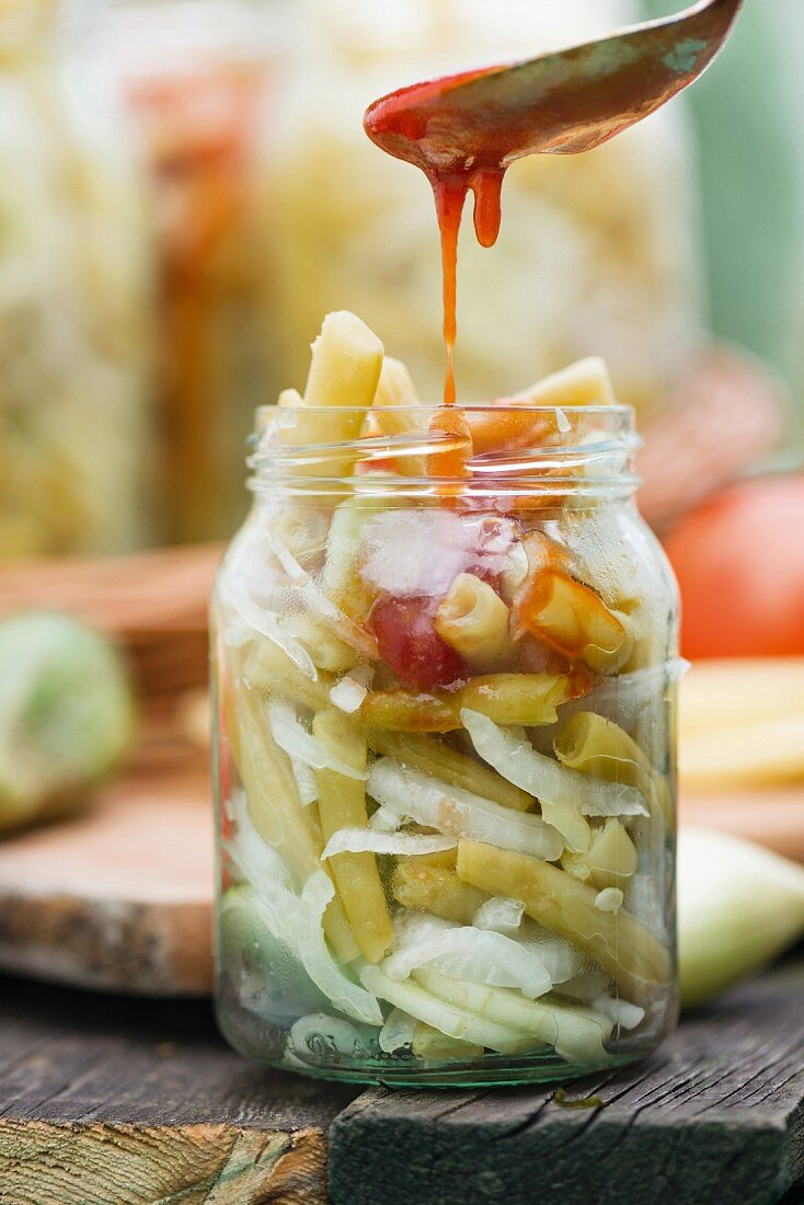 Bean and cucumber salad with onions and tomato sauce, in a jar