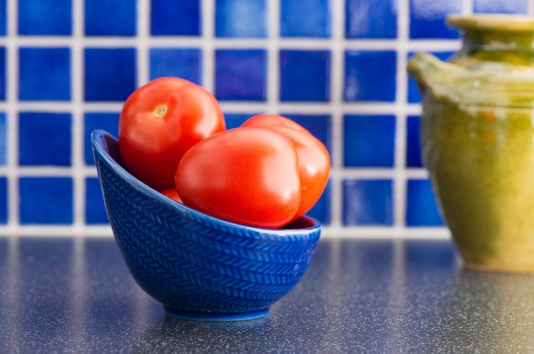Plum tomatoes in bowl on kitchen counter