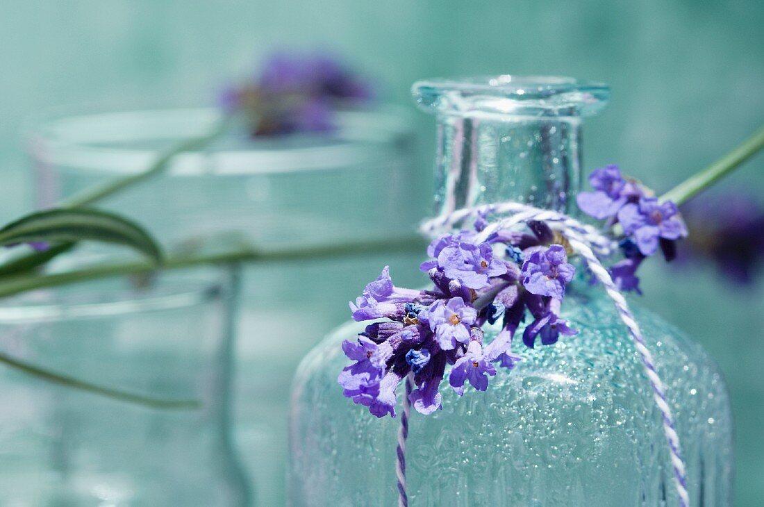A sprig of lavender on a bottle of scented oil