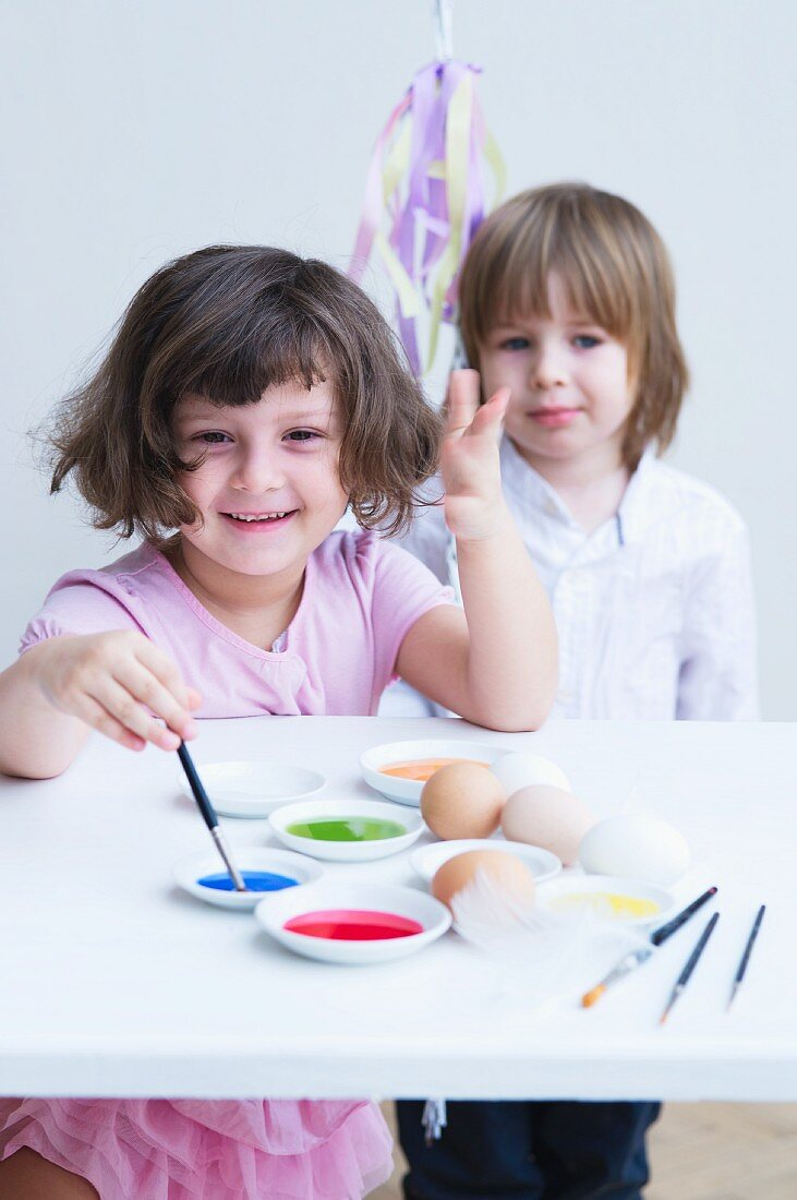 Smiling girl with paintbrush and paint; smiling child with toy in background