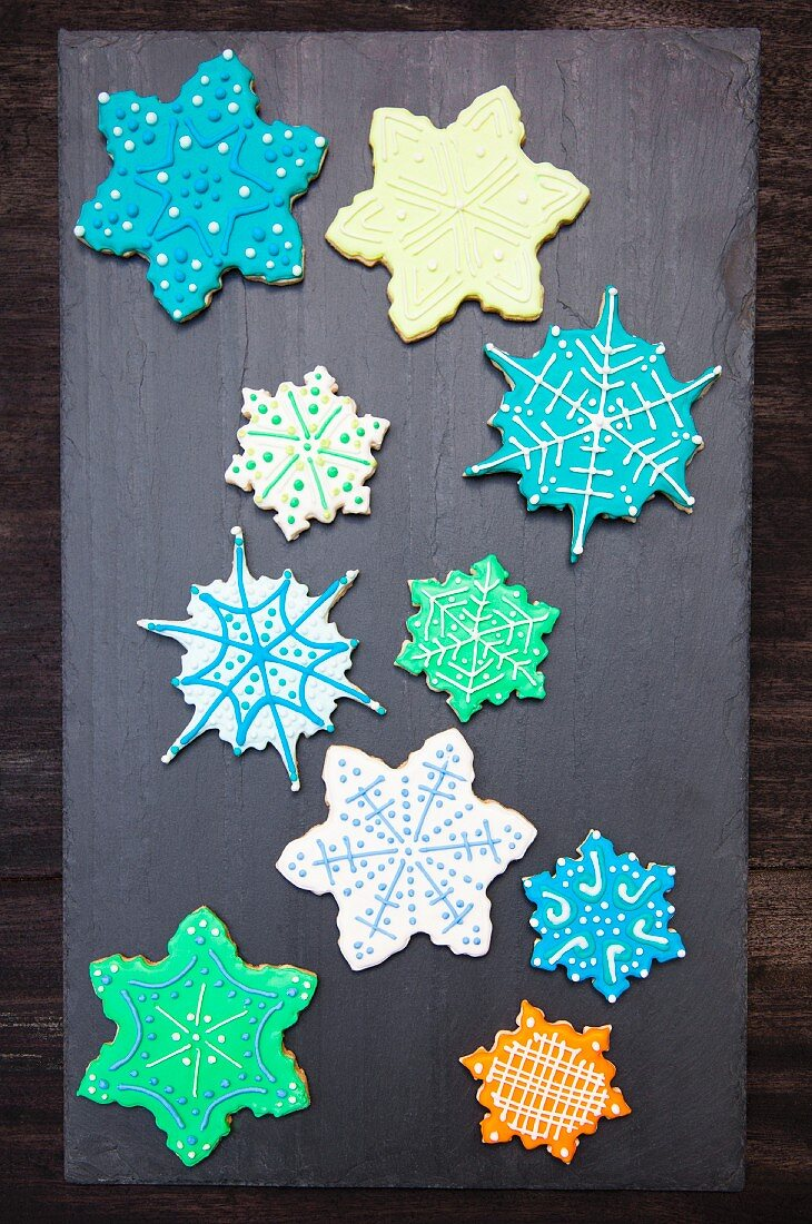 Snowflake Sugar Cookies hand decorated and displayed on a slate rock
