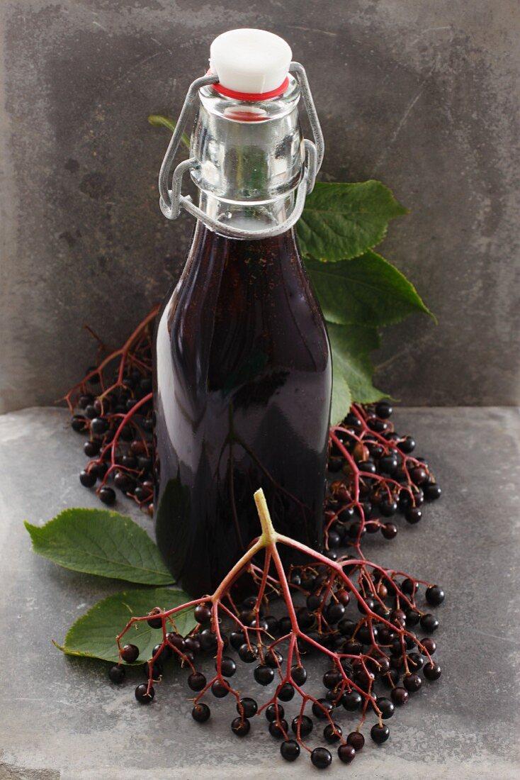 A bottle of elderberry juice and fresh elderberries