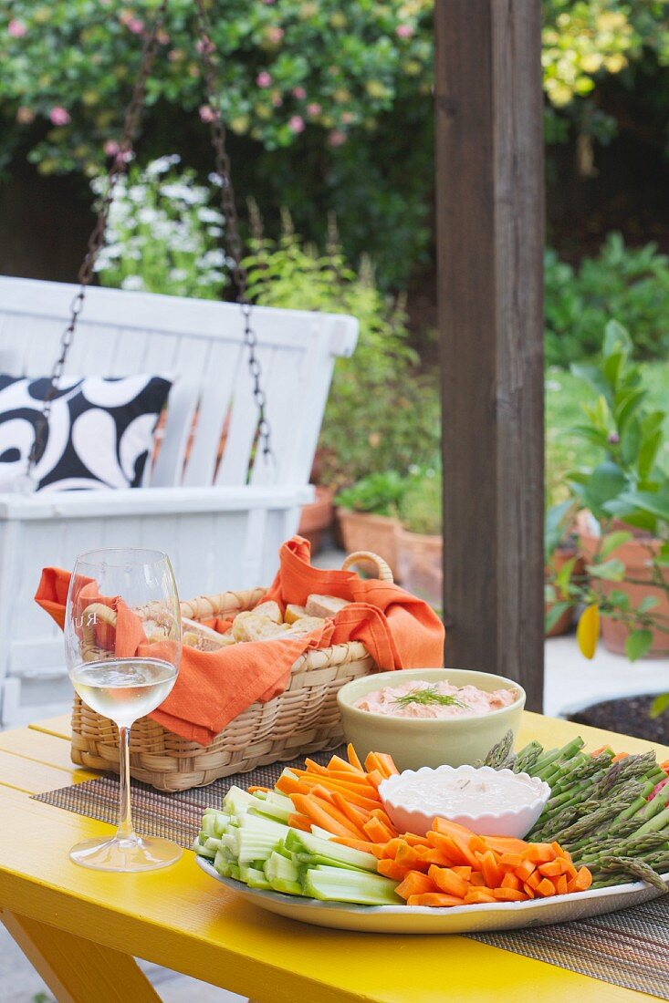 A bread basket, a plate of crudités with dips, and a glass of wine on a table on the patio