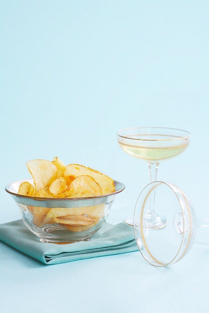Potato crisps in a glass bowl served with a glass of champagne