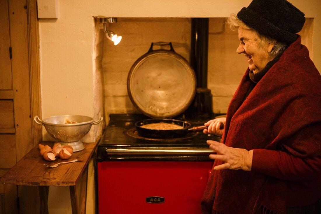 Elderly woman cooking Spanish omelette (tortilla)