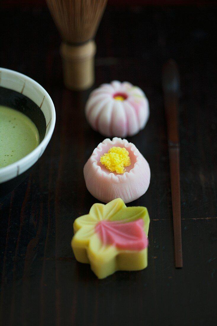 A wagashi maple leaf, camomile and a chrysanthemum, a tea whisk, a matcha spoon and matcha tea