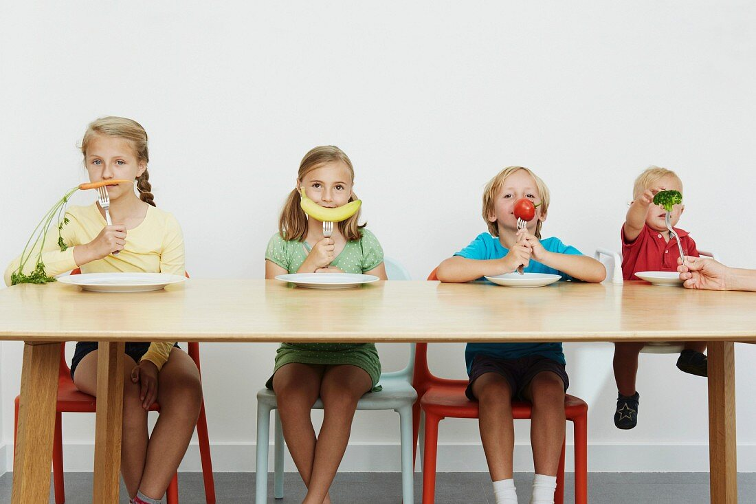 Four children sitting at table with vegetables on forks