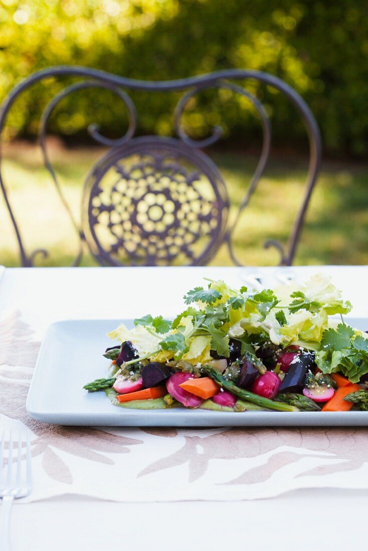 A Spring Vegetable Salad on a Platter on an Outdoor Table