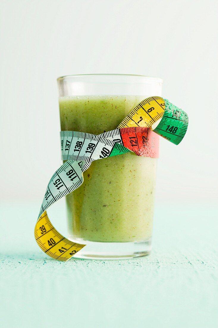 Apple and kiwi smoothie in a glass with a measuring tape