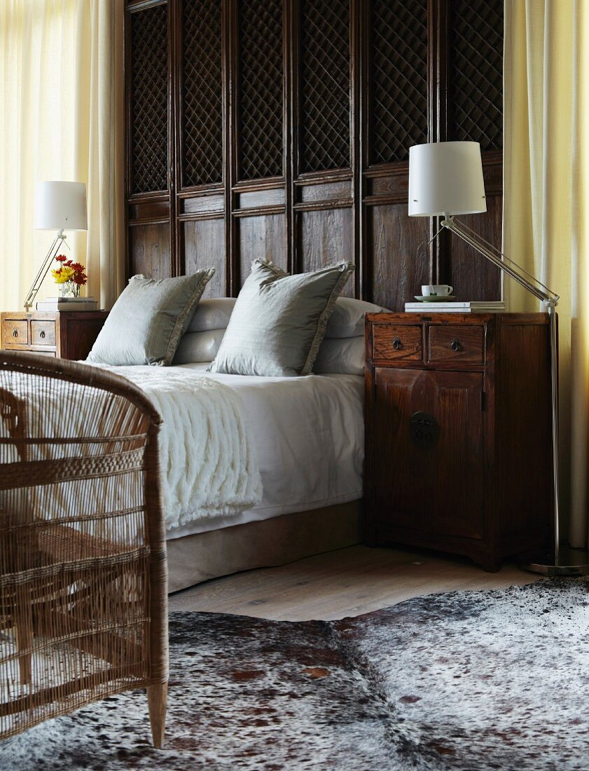 A high double bed in front of antique wood panelling with antique bedside cabinets to either side; a modern angle-poise floor lamp next to each bedside cabinet