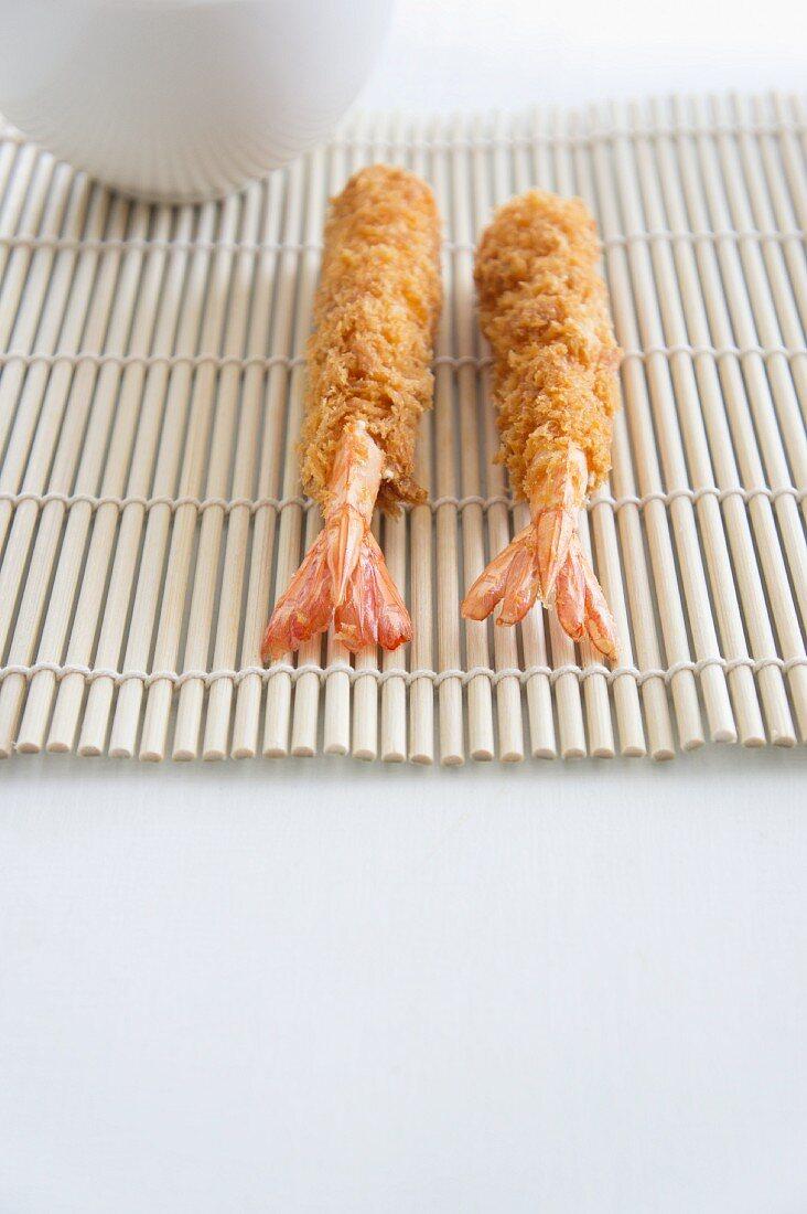 Tempura prawns on a bamboo mat
