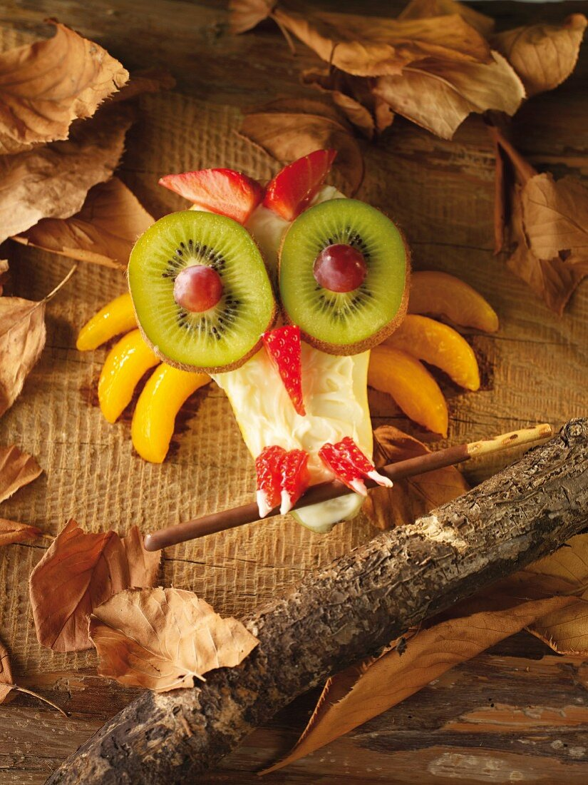 A fruit owl surrounded by autumn leaves