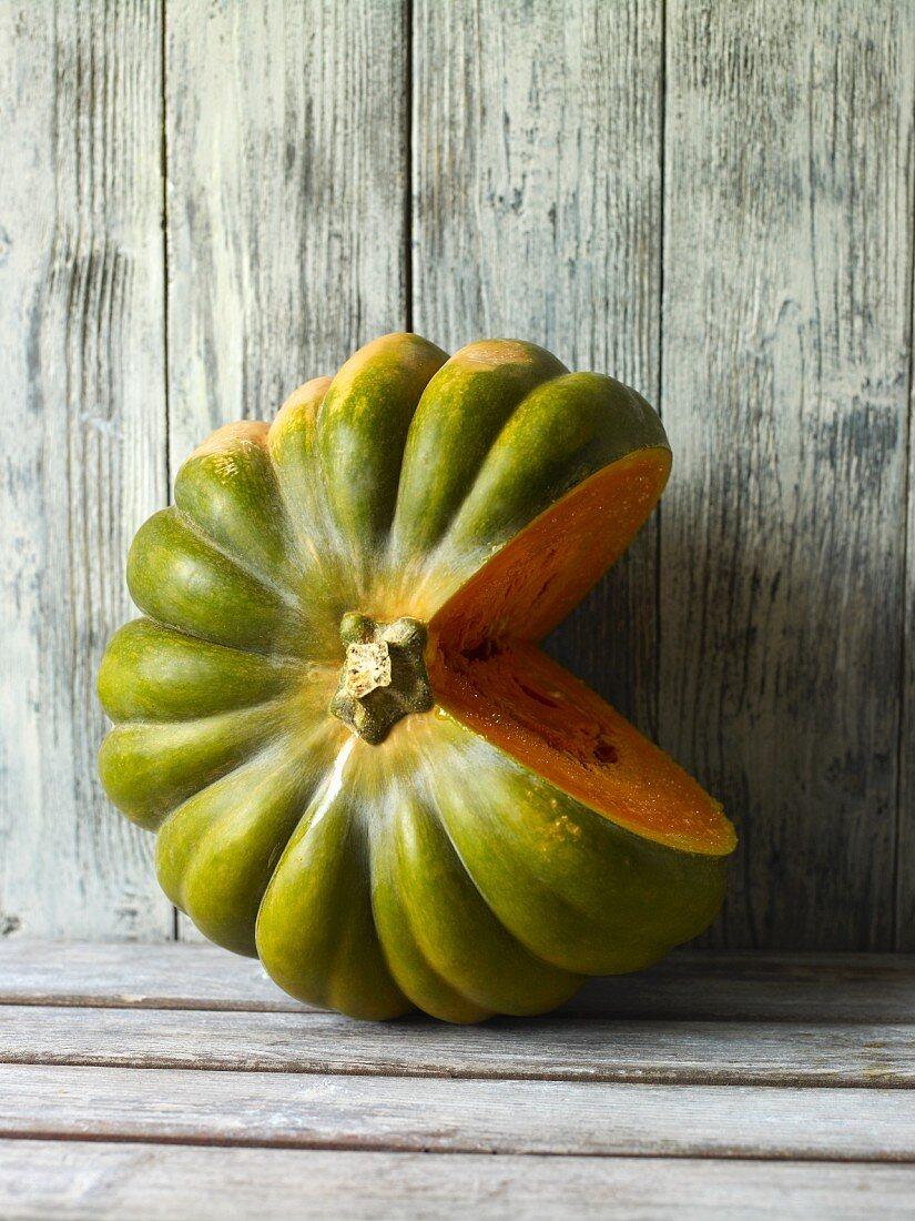 A green winter squash, cut open, against a wooden wall