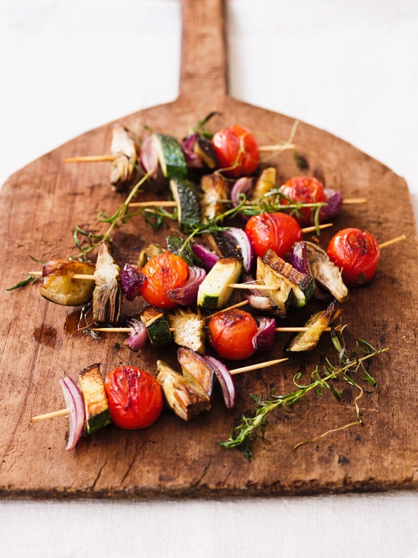 Vegetable skewers with cherry tomatoes, courgette and onions on a wooden bread peel